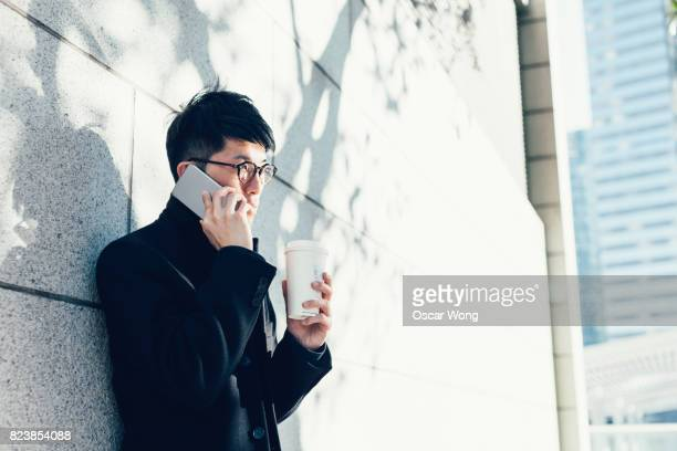 Young businessman talking on phone and taking coffee break in park