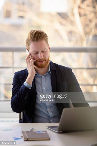 Young businessman talking on phone in his office