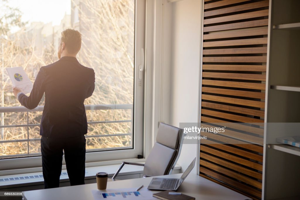 Young businessman talking on phone near the window : Stock Photo