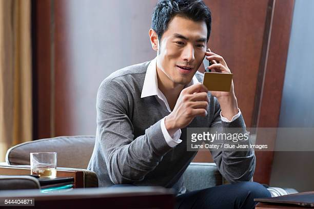Young businessman talking on phone with a business card