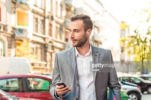 Junger Geschäftsmann sprechen auf smart phone in der Stadt
