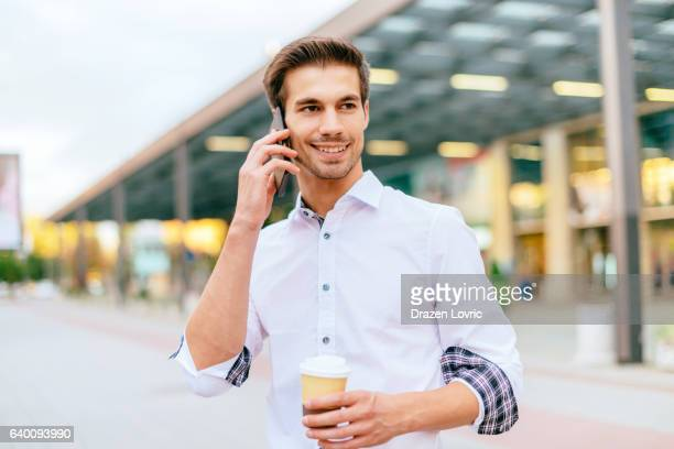 young businessman talking on smartphone on street near office building - drazen stock pictures, royalty-free photos & images