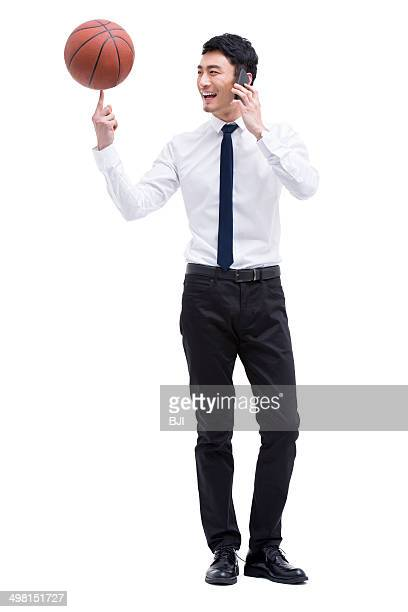 Young businessman talking on the phone with a spinning basketball on finger