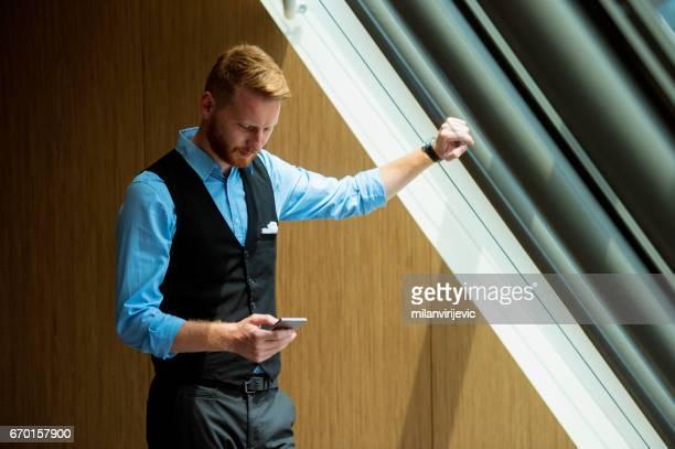Message de SMS du jeune homme d'affaires près de la fenêtre