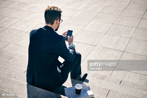 Young businessman texting while sitting on stairs