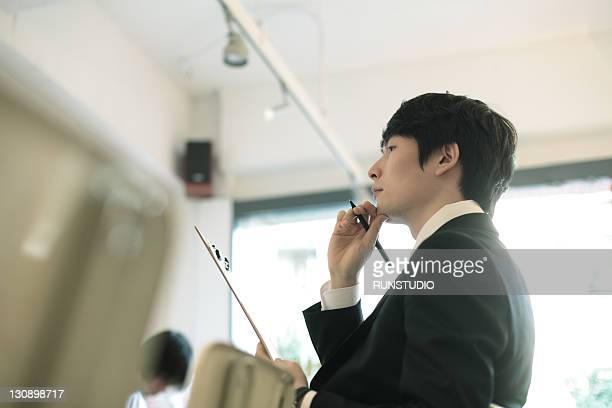young businessman thinking with a pen - ビジネスマン ストックフォトと画像