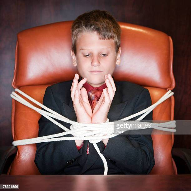 young businessman tied to chair - restraining stock photos and pictures