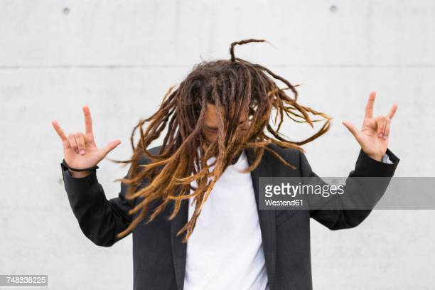 Young businessman tossing his dreadlocks showing Rock And Roll Sign
