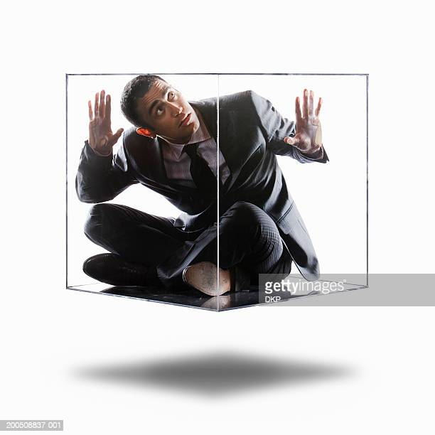 Young businessman trapped inside transparent box, looking up