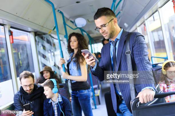 young businessman traveling to work and using smart phone - melbourne australia stock pictures, royalty-free photos & images