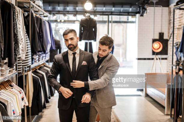 young businessman trying on a new suit - custom tailored suit stock pictures, royalty-free photos & images
