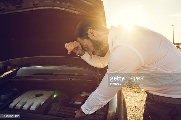 Young businessman trying to fix his car at sunset.
