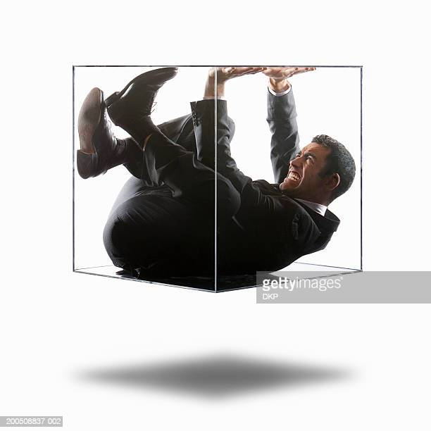young businessman trying to push his way out of transparent box - claustrofobia fotografías e imágenes de stock