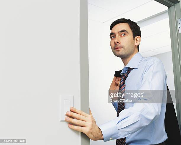 Young businessman turning off light in office