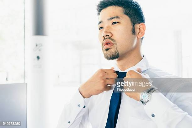 Young Businessman Tying His Tie