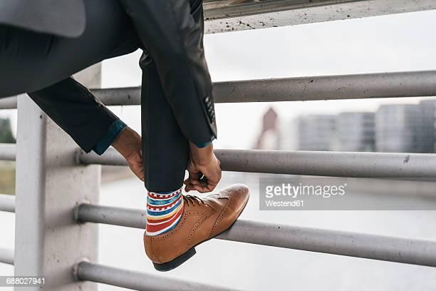 young businessman tying shoe laces - leren schoen stockfoto's en -beelden
