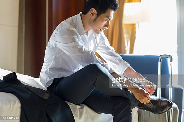 young businessman tying shoes in hotel room - colletto aperto foto e immagini stock