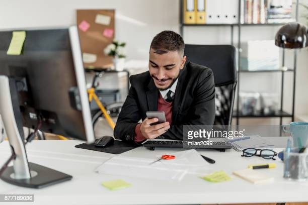 young businessman typing a message in his office - milan2099 stock photos and pictures