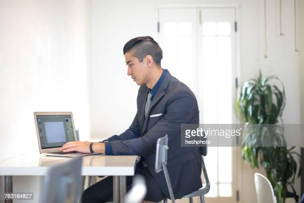 young businessman typing on laptop at desk - heshphoto stock-fotos und bilder