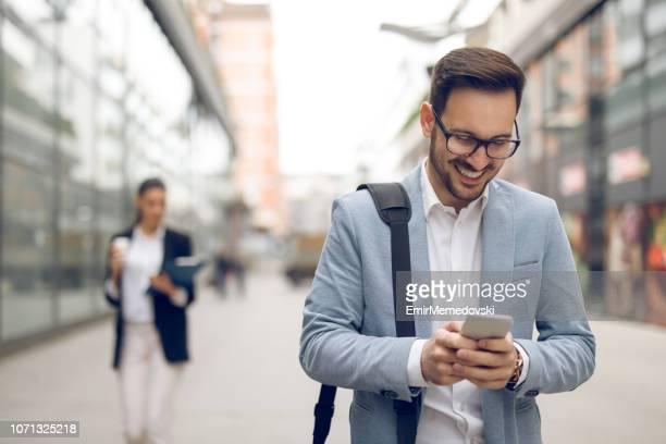 年輕的商人在上班的路上輸入短信 - 男商人 個照片及圖片檔