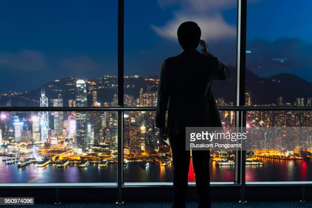 young businessman using a cellphone standing alone in an office at night in front of windows overlooking the city - front view ストックフォトと画像