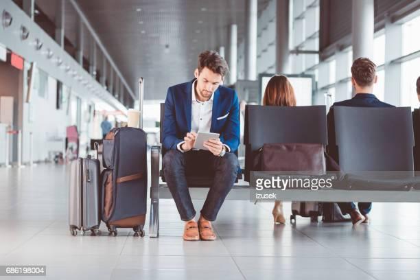 空港の待合室でデジタル タブレットを使用して青年実業家