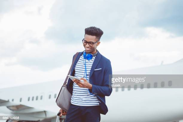 Young  businessman using a digital tablet in front of airplane