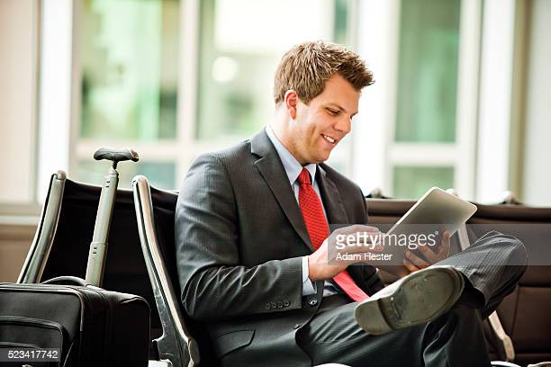 A young businessman using a tablet device while traveling.