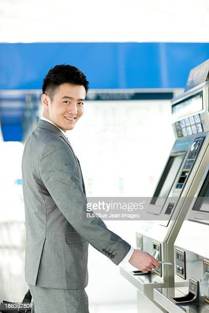 Young businessman using automatic ticket machine at subway station