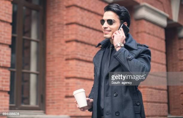 Young businessman using cell phone in city