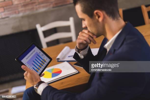 Jeune homme d'affaires, à l'aide de tablette numérique et analyse d ' affaires.