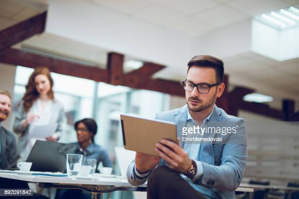 young businessman using digital tablet and analyzing business report. - analysing stock pictures, royalty-free photos & images