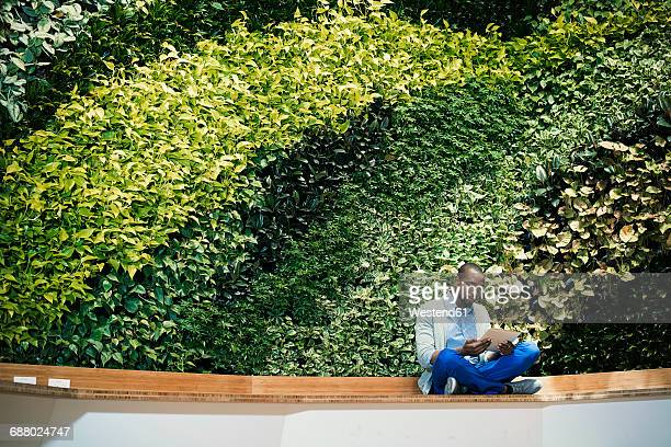 Young businessman using digital tablet in front of green plant wall