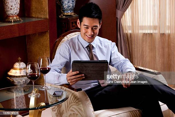 Young businessman using digital tablet in hotel