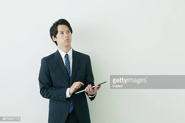 Young businessman using digital tablet, looking up