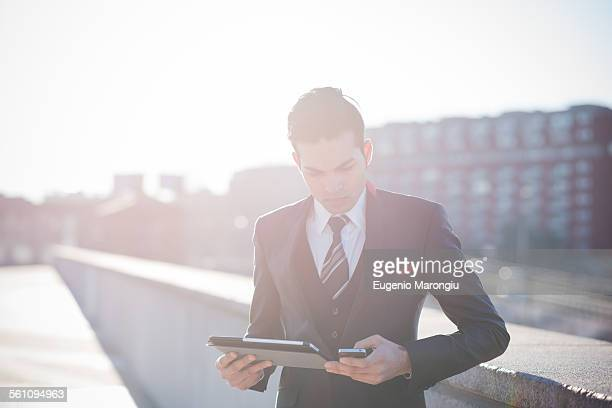 Young businessman using digital tablet on rooftop