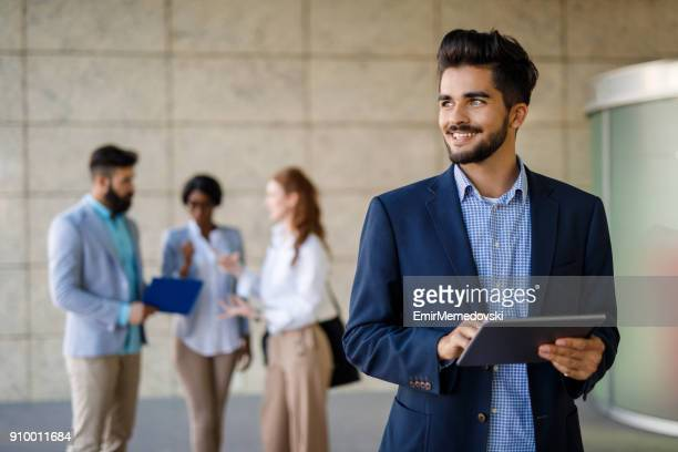 young businessman using digital tablet outdoors - emir memedovski stock pictures, royalty-free photos & images