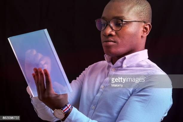 young businessman using futuristic portable device - futurism stock photos and pictures