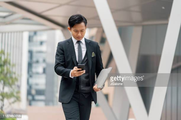 Young businessman using his phone outdoors