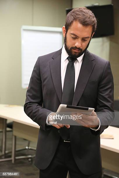 young businessman using his tablet computer - economist stock pictures, royalty-free photos & images