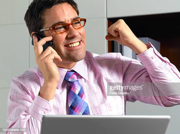 Young businessman using laptop and mobile phone, gesturing and smiling