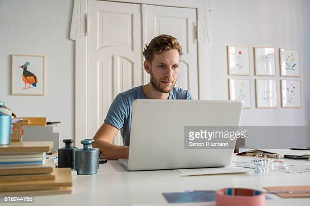 young businessman using laptop at work - laptop stock-fotos und bilder