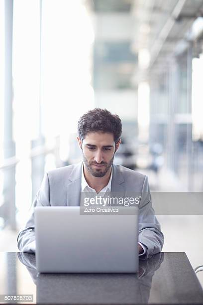 Young businessman using laptop in conference centre