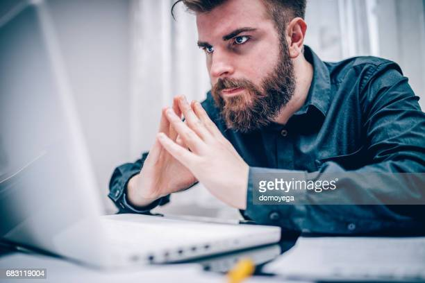 young businessman using laptop in the office - home icon stock photos and pictures
