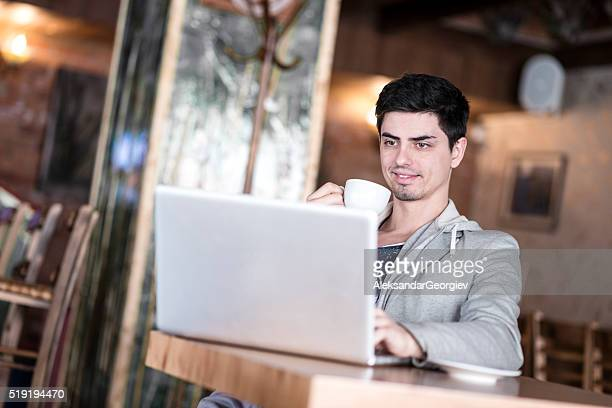 young businessman using laptop on a break in a cafe - aleksandar georgiev stock photos and pictures