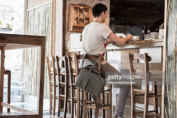 Young Businessman Using Laptop on a Break in a Cafe