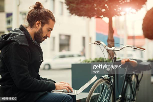 young businessman using laptop outdoors. - man bun stock pictures, royalty-free photos & images