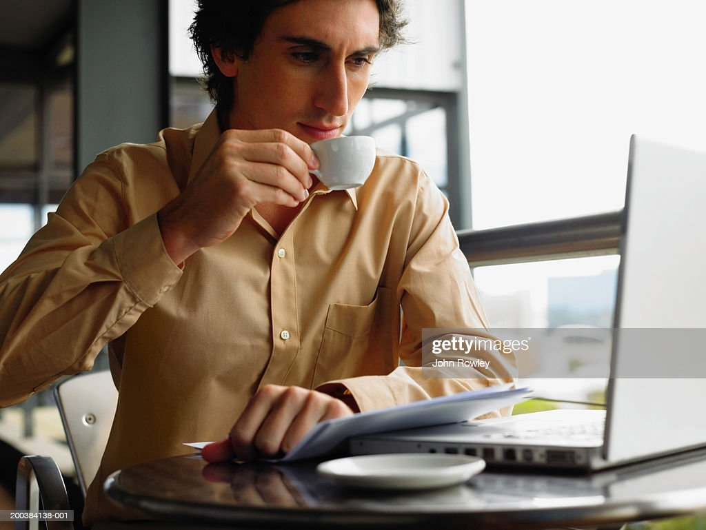Young businessman using laptop sitting at table drinking coffee : Stock Photo