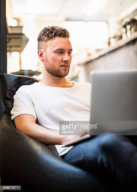 Young businessman using laptop while sitting on bean bag in new office