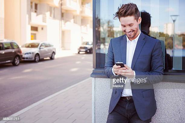 Young businessman using mobile phone against wall by sidewalk